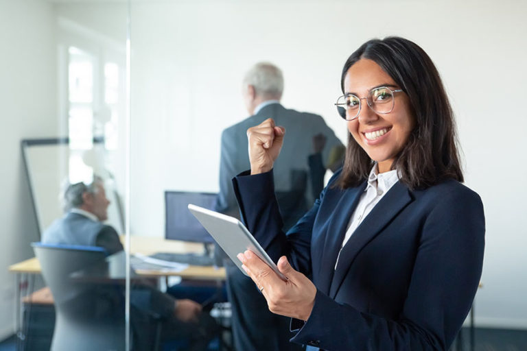 happy-female-professional-glasses-suit-holding-tablet-making-winner-gesture-while-two-businessmen-working-glass-wall-copy-space-communication-concept
